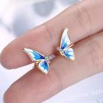 Sinistes toonides liblikatiibadega kõrvarõngad lähedalt vaates
